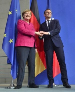 German Chancellor Angela Merkel and French President Emmanuel Macron shake hands after addressing a press conference after talks at the chancellery in Berlin on May 15, 2017, a day after the new French president took office. Emmanuel Macron is on his first trip abroad as French president. / AFP PHOTO / John MACDOUGALL